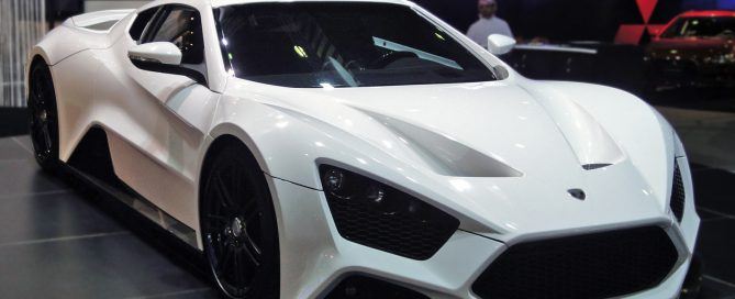 A gleaming, white Zenvo ST1 sits in a grey garage.