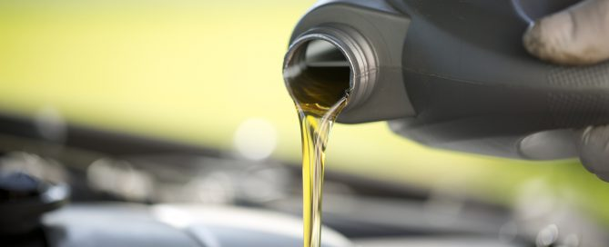 A fresh quart of oil is poured into a car engine, elegantly.