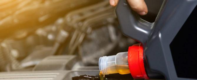 putting motor oil into the car during an oil change.